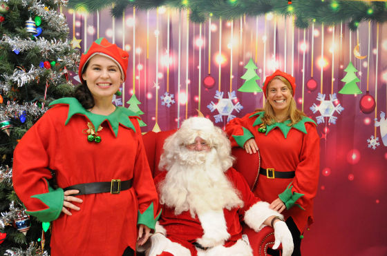 Santa Claus visits with Jisselle Perdomo (left), ESL instructor at the Siler City Center, and Julia Herbon (right), Lead ESL Instructor for Chatham County, during Central Carolina Community College's Christmas Tree Light celebration at the Siler City Center.